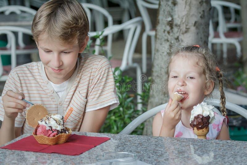 Irmãos do menino e da menina que apreciam seu gelado italiano no gelateria fotos de stock