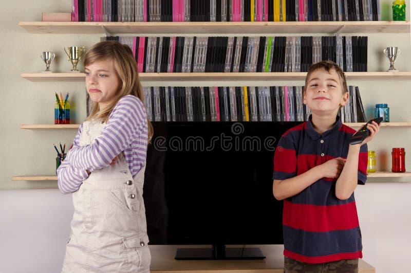 Irmãos e o controlo a distância da tevê imagens de stock