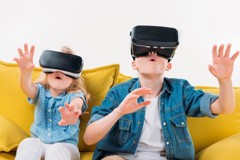 irmãos entusiasmado que usam auriculares e assento da realidade virtual imagens de stock royalty free