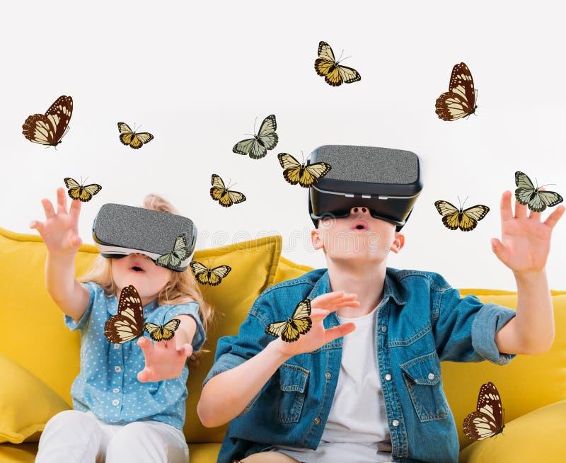 irmãos entusiasmado que usam auriculares e vista da realidade virtual fotos de stock royalty free