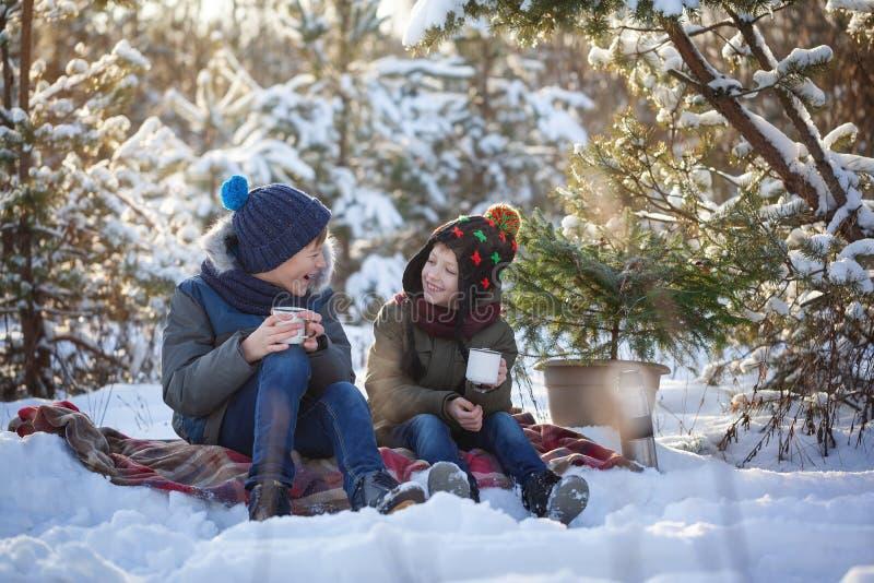 Irmãos felizes da família dois em uma caminhada do inverno que bebem fora o chocolate foto de stock