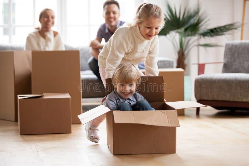 Irmãos felizes que jogam a equitação na caixa que move-se na casa nova fotos de stock