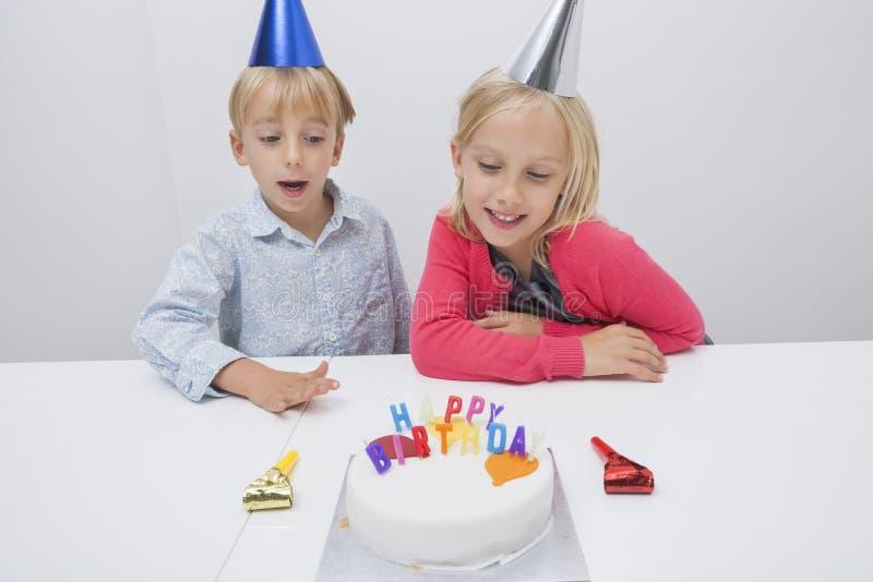 Irmãos felizes que olham o bolo de aniversário na tabela na casa imagens de stock royalty free
