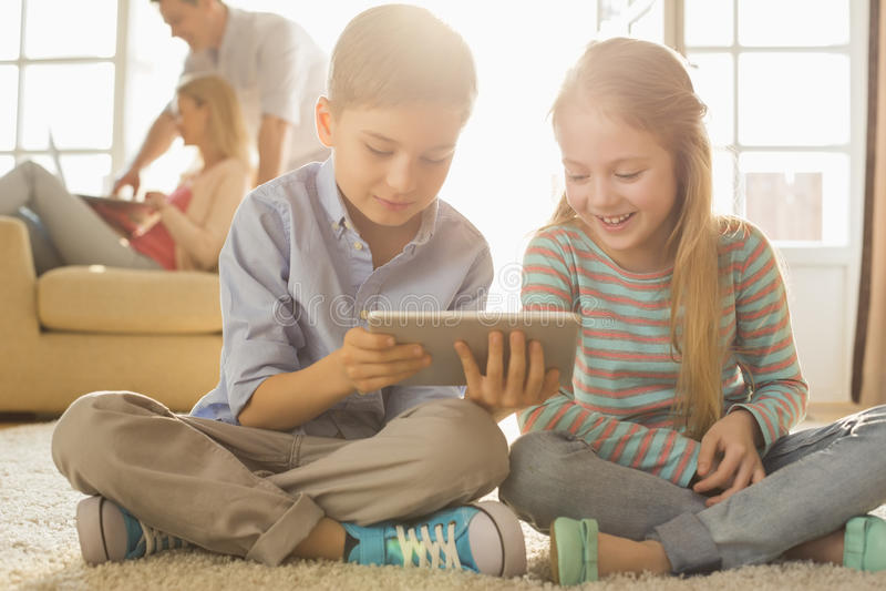 Irmãos felizes que usam a tabuleta digital no assoalho com pais no fundo imagem de stock royalty free