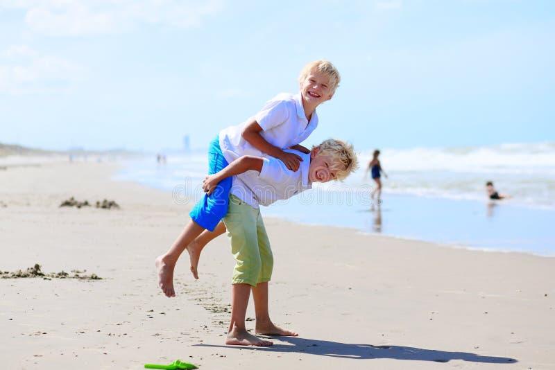 Irmãos gêmeos que jogam na praia imagem de stock