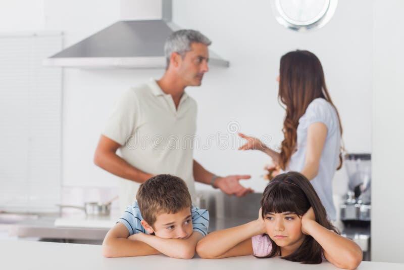 Irmãos infelizes que sentam-se na cozinha com seus pais que são f fotografia de stock royalty free