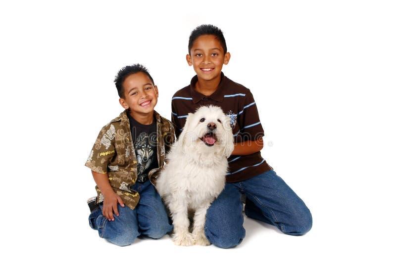 Irmãos latino-americanos com seu cão no branco imagens de stock royalty free