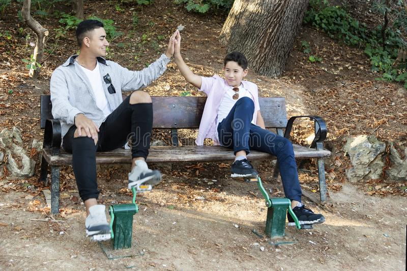 Irmãos no parque no por do sol fotos de stock royalty free
