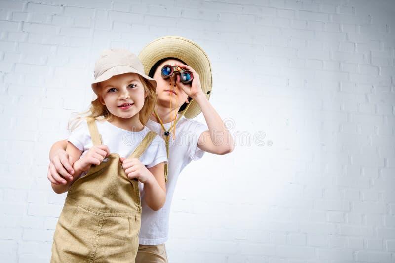 irmãos nos trajes do safari que abraçam e que olham foto de stock