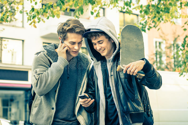 Irmãos novos dos melhores amigos do moderno que têm o divertimento com smartphone imagens de stock
