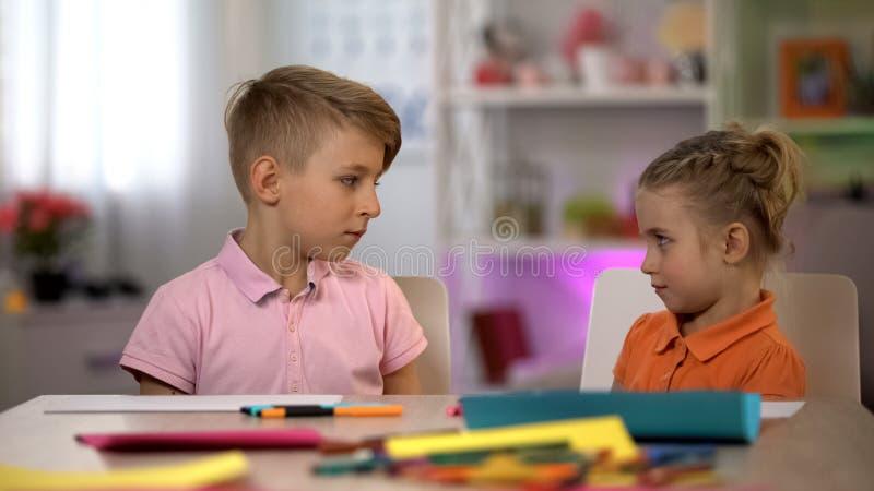 Irmãos ofendidos que olham se, crianças que discutem, engano imagem de stock royalty free