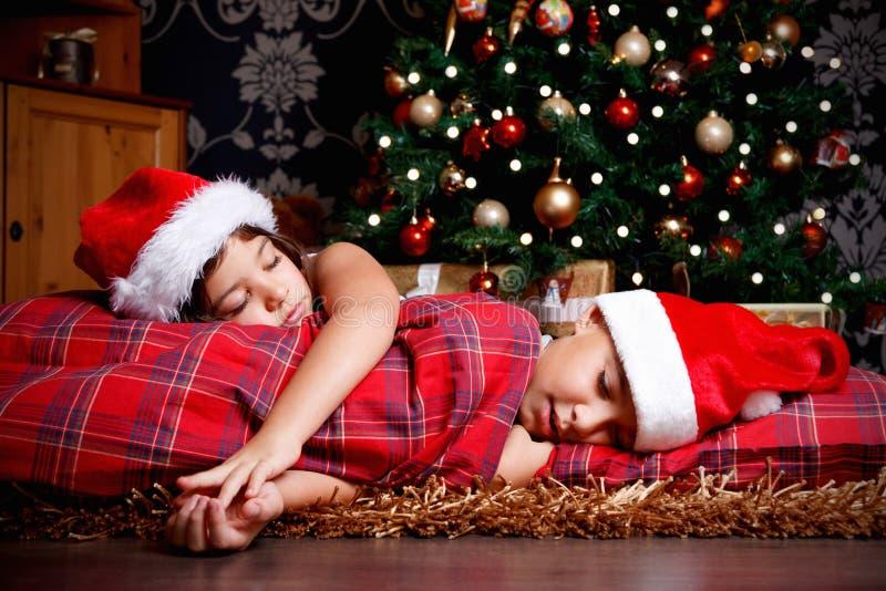Irmãos pequenos adormecidos ao esperar presentes fotografia de stock