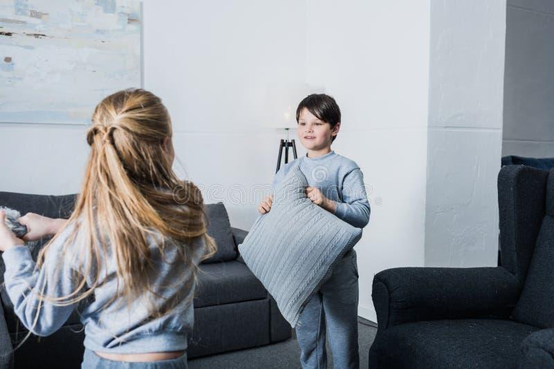 Irmãos pequenos nos pijamas que lutam com descansos em casa foto de stock