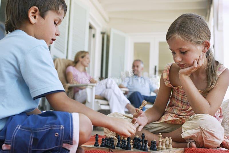 Irmãos pequenos que jogam a xadrez no patamar imagem de stock