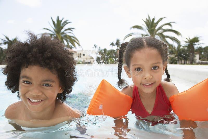 Irmãos que apreciam na piscina imagem de stock