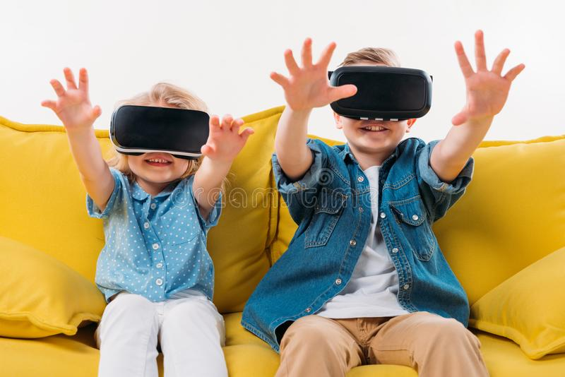 irmãos que gesticulam e que usam auriculares da realidade virtual ao sentar-se imagem de stock