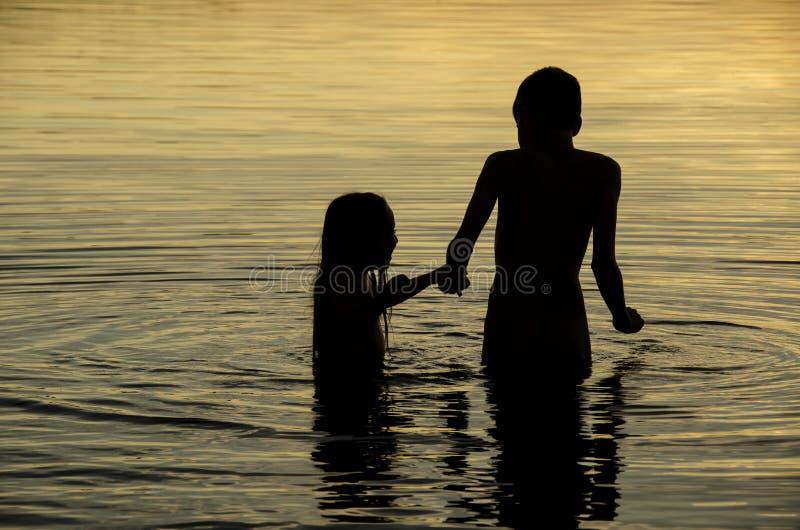 Irmãos que guardam as mãos na água de um lago no por do sol foto de stock