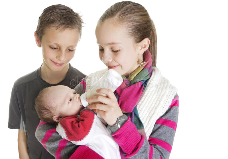 Irmãos que importam-se com seu irmão novo do bebê fotos de stock royalty free