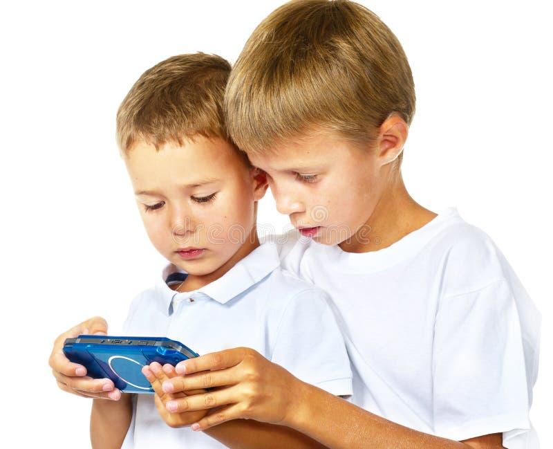 Irmãos que jogam console handheld do jogo foto de stock royalty free