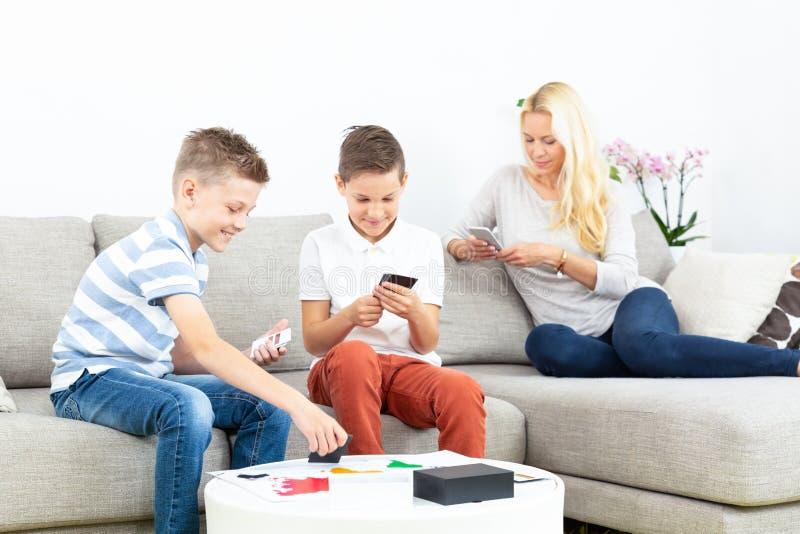 Irmãos que jogam o jogo de cartas no sofá da sala de visitas em casa supevised por sua mãe imagens de stock