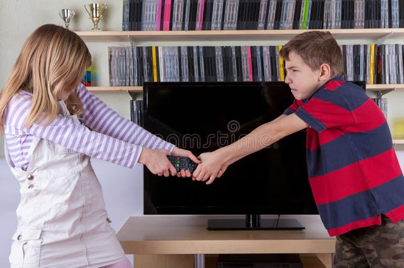 Irmãos que lutam desperatelly pelo controlo a distância da tevê no fron imagens de stock