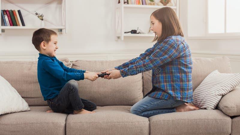 Irmãos que lutam sobre o controlo a distância em casa foto de stock royalty free
