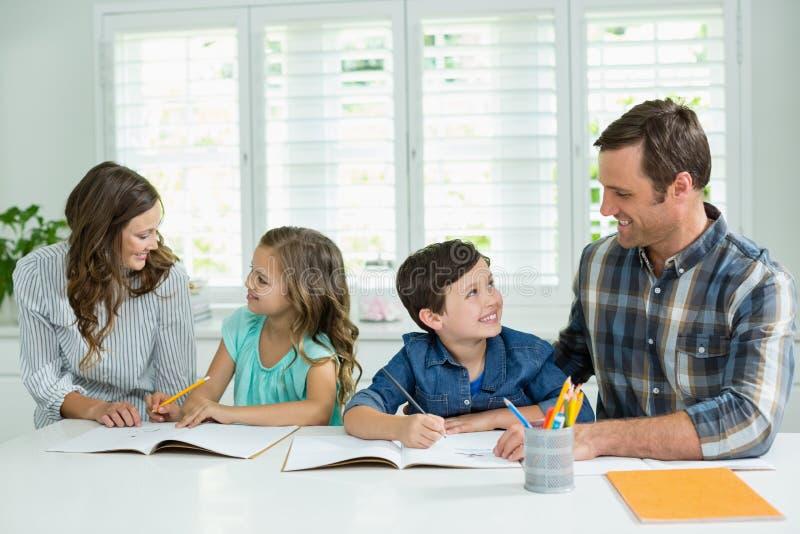Irmãos que obtêm a ajuda com trabalhos de casa dos pais foto de stock