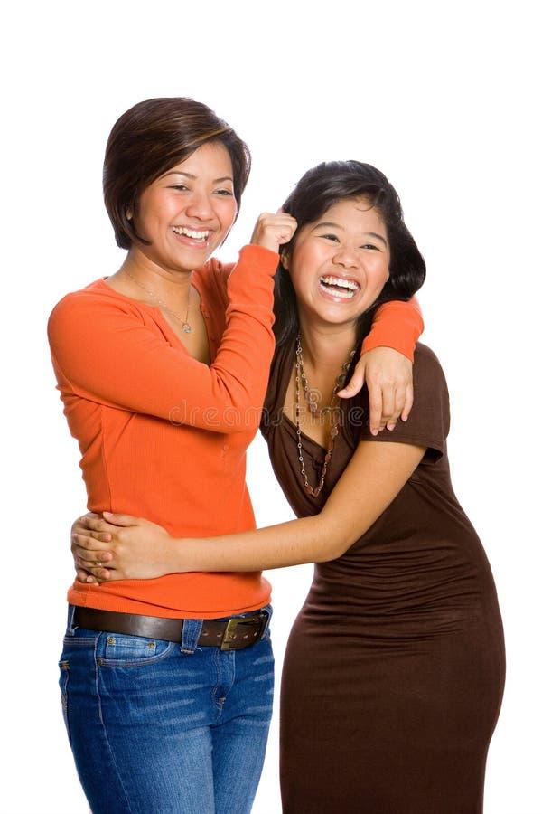 irmãs asiáticas bonitas que têm o divertimento isolado foto de stock