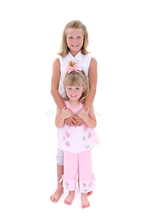 Irmãs bonitas na cor-de-rosa sobre o branco foto de stock royalty free