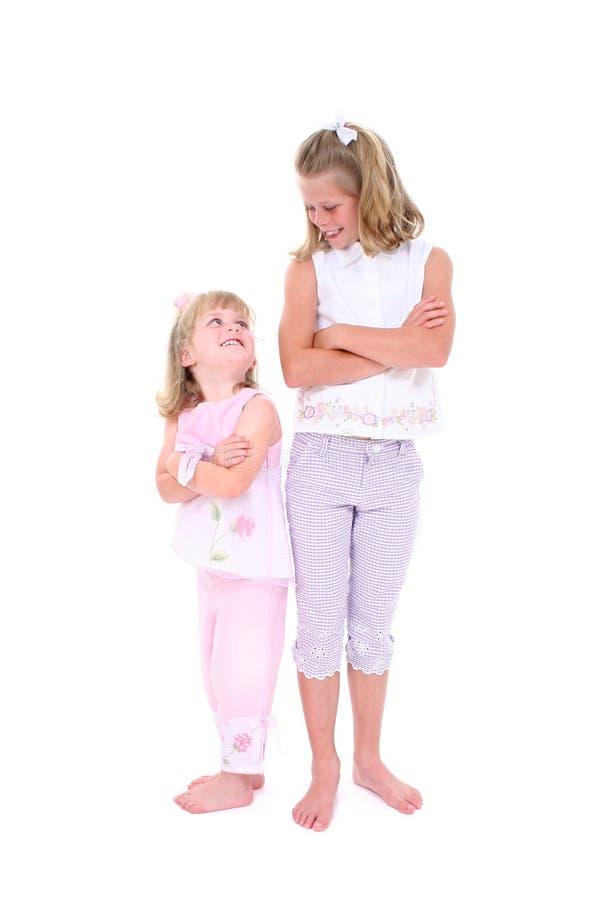 Irmãs bonitas na cor-de-rosa sobre o branco imagem de stock royalty free
