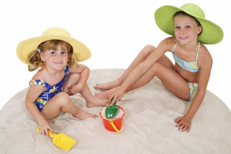 Irmãs bonitas nos chapéus da praia que jogam na areia imagem de stock royalty free