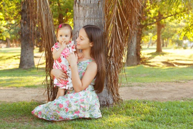 Irmãs bonitos adolescentes e bebê que joga na grama verde imagens de stock