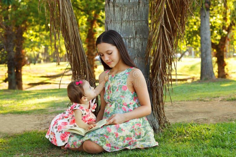 Irmãs bonitos adolescentes e livro de leitura do bebê fotografia de stock royalty free