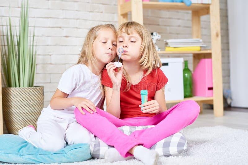 Irmãs bonitos que fundem bolhas imagem de stock