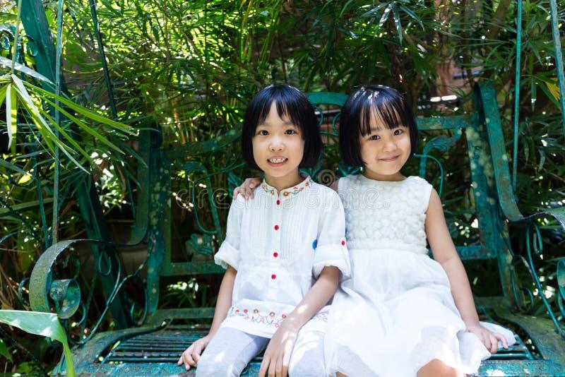 Irmãs chinesas pequenas asiáticas que sentam-se no banco foto de stock
