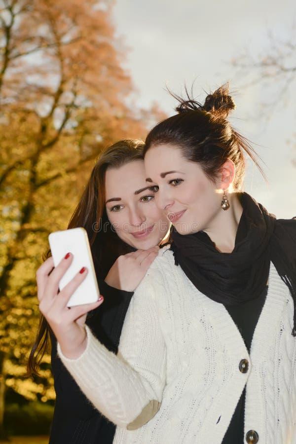 Irmãs com smartphone foto de stock royalty free