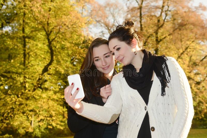 Irmãs com smartphone imagem de stock