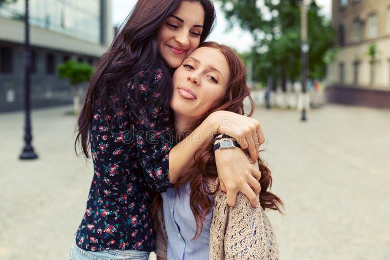 Irmãs de sorriso despreocupadas que abraçam e que têm o divertimento junto fotografia de stock