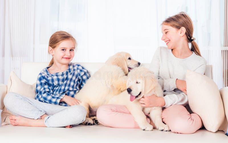 Irmãs de sorriso que sentam-se com cachorrinhos foto de stock royalty free