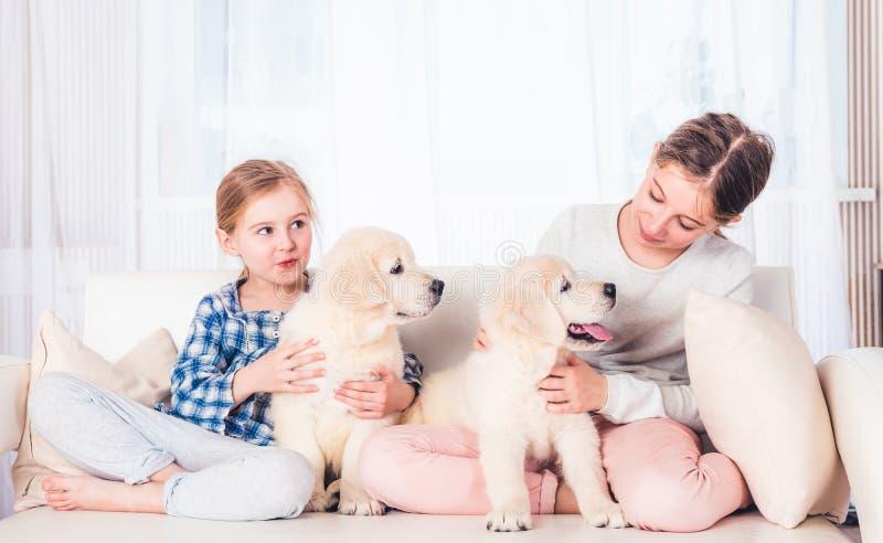 Irmãs de sorriso que sentam-se com cachorrinhos fotos de stock