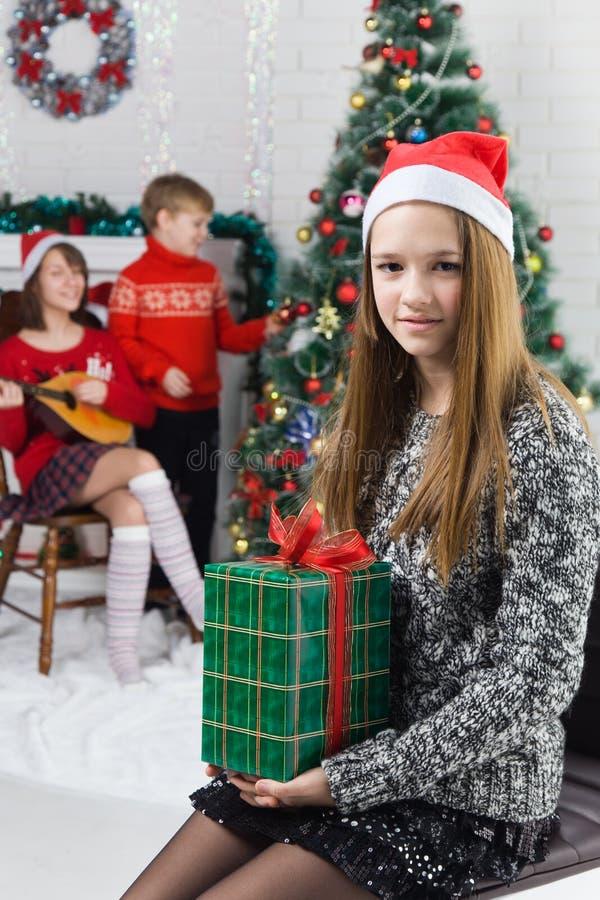 Irmãs e irmão ao lado da árvore de Natal foto de stock royalty free