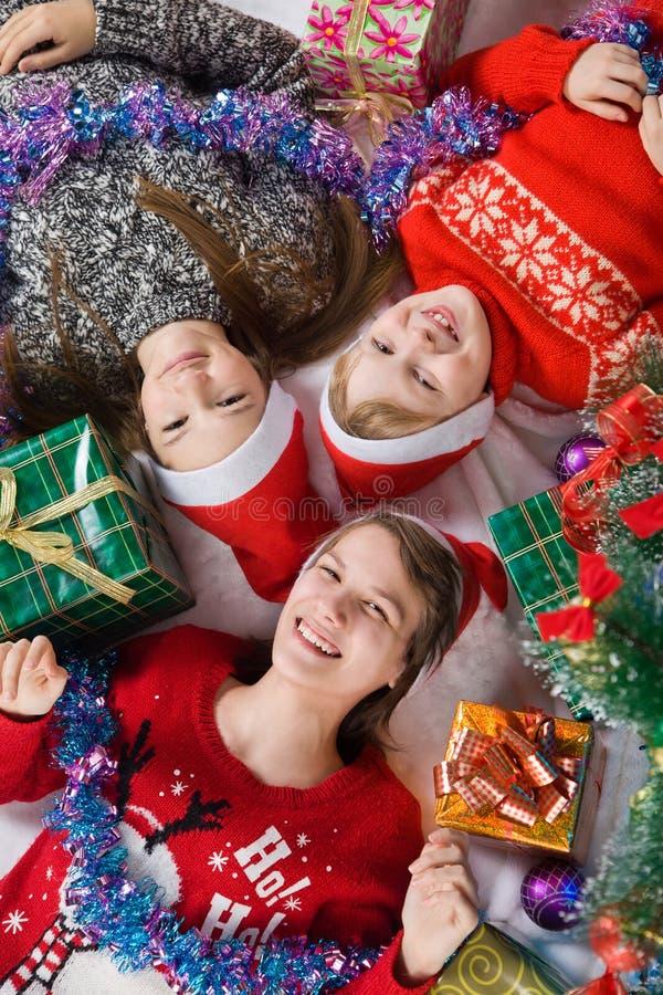 Irmãs e irmão ao lado da árvore de Natal imagem de stock royalty free