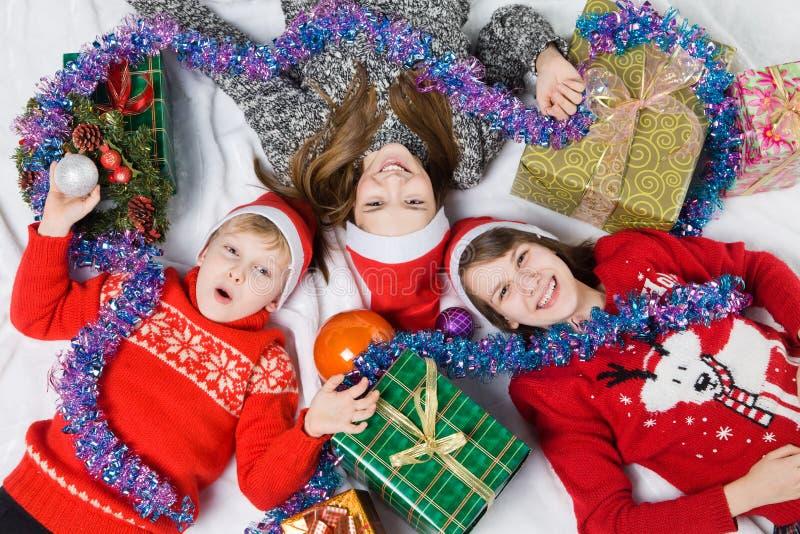 Irmãs e irmão ao lado da árvore de Natal imagem de stock