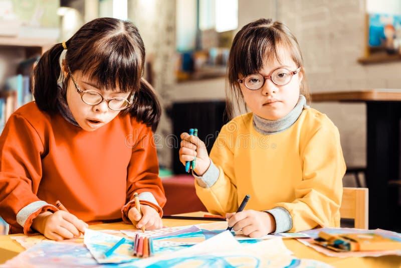 Irmãs focalizadas com a Síndrome de Down que veste camisetas alaranjadas e amarelas fotos de stock royalty free