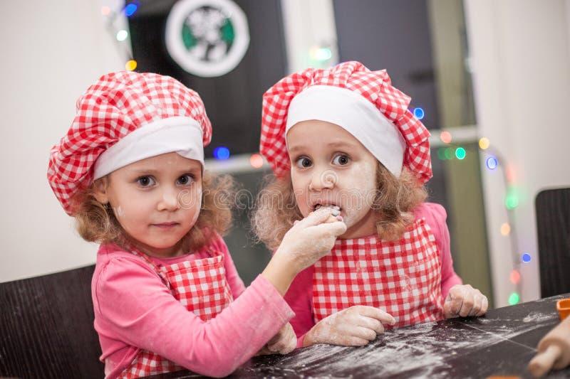 Irmãs gêmeas idênticas das crianças felizes que encarregam biscoitos na cozinha, foto ocasional na vida real interior, família no imagens de stock