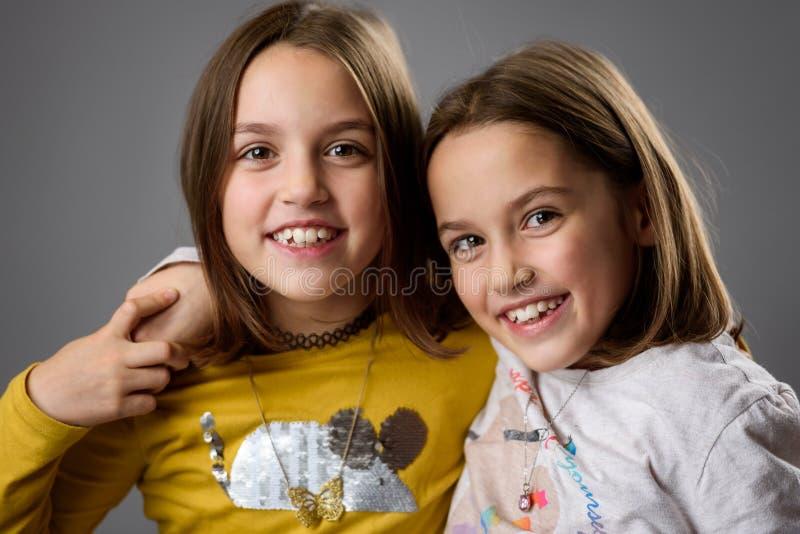 Irmãs gêmeas idênticas estão se posando para a câmera fotos de stock