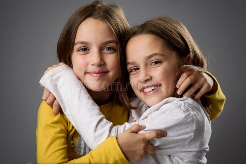 Irmãs gêmeas idênticas estão se posando para a câmera foto de stock royalty free