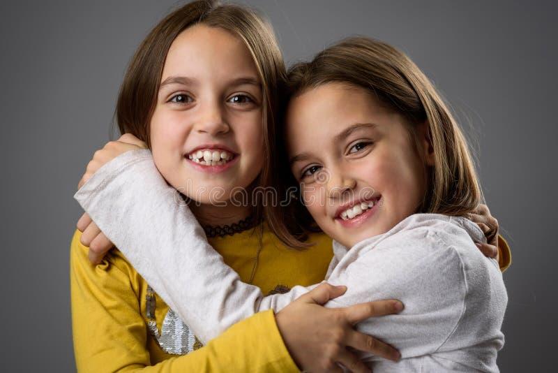 Irmãs gêmeas idênticas estão se posando para a câmera fotos de stock royalty free