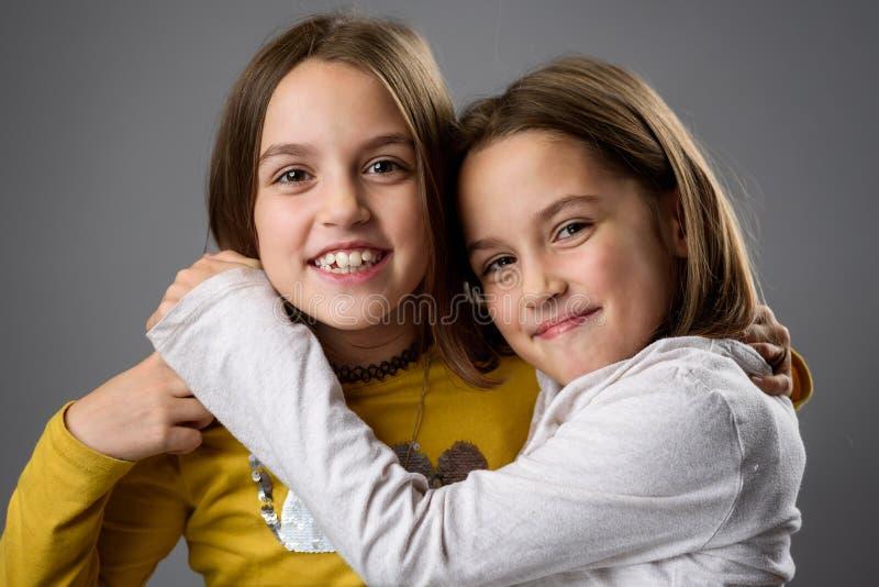 Irmãs gêmeas idênticas estão se posando para a câmera imagens de stock