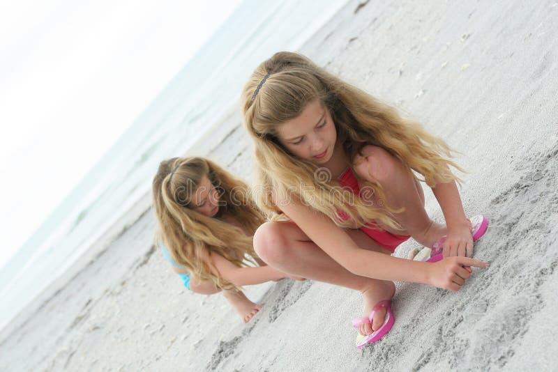 Irmãs gêmeas que jogam na areia imagem de stock